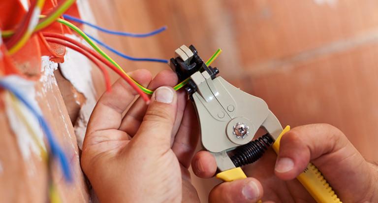 мужчина режет провода